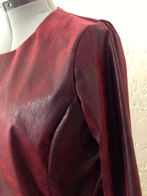 A close up view of the sleeve, neckline and side panel.
